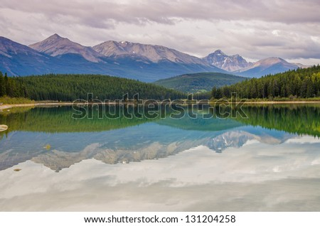Rolling mountain peaks reflecting onto a lake
