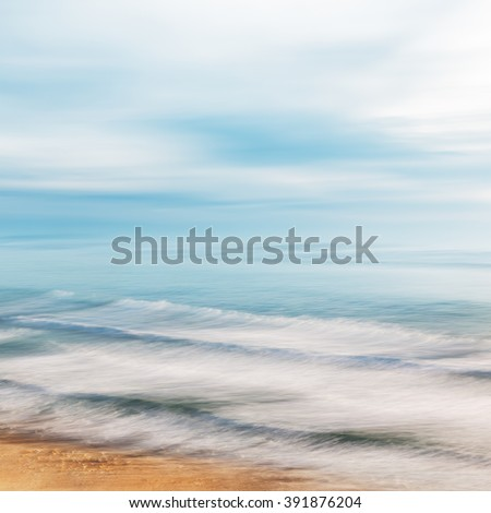 Rolling ocean waves breaking along the coast of California with a moody sky.  Image features blurred panning motion combined with a long exposure. - stock photo