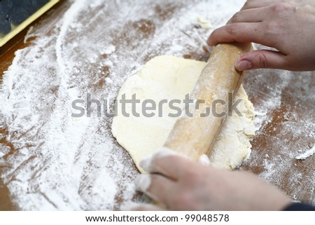 Rolling out cookie dough on a cutting board - stock photo