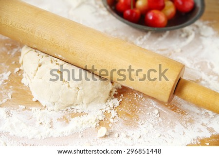 Rolling out dough  on floured surface for a cherry pie - stock photo