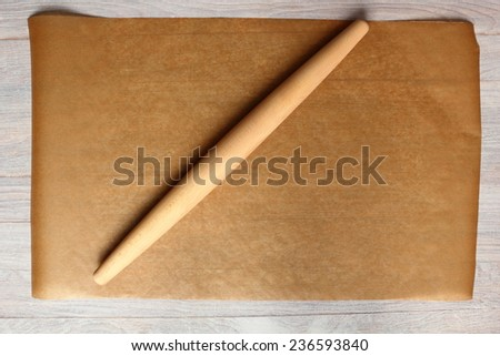 Rolling Pin and Baking Paper. Making Meat Pie from Yeast Dough. - stock photo