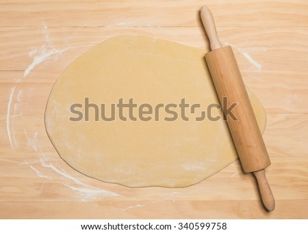 rolling pin and dough on wooden background - stock photo