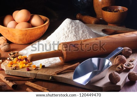 Rolling pin, flour and ingredients on an old wooden board in a rustic kitchen - stock photo