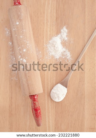 Rolling pin on table with wooden spoon and flour. - stock photo