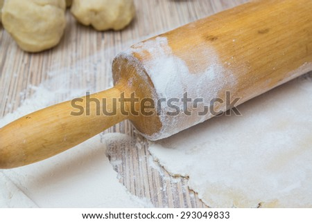 rolling pin with dough and flour on a table. Preparing a baking