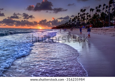 Rolling waves and the sun casting an orange hue on the horizon 3 - stock photo