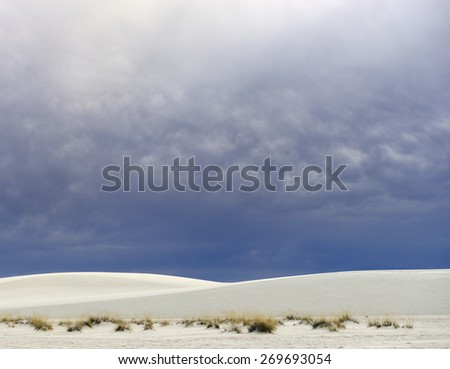 Rolling White Sand Dunes and Dramatic Clouds - stock photo