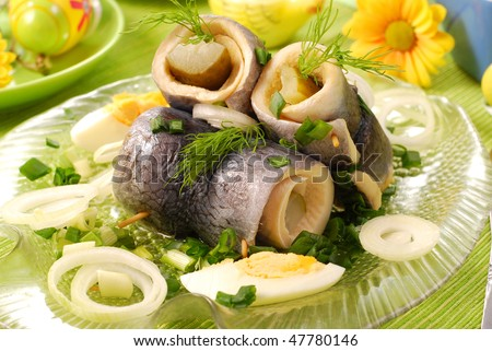 rollmops with gherkins on fish shape plate for easter