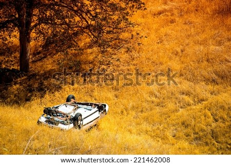 Rollover Compact Car Crash. White Crashed Car in the Mountain Road Ditch in California, USA. Traffic Accident. - stock photo