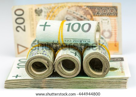 rolls and stack of banknotes - polish zloty - 100 and 200 pln
