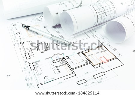 Rolls of blueprints and architectural drawings with pencil - stock photo