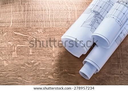 Rolls of blueprints on wooden oaken board construction concept  - stock photo