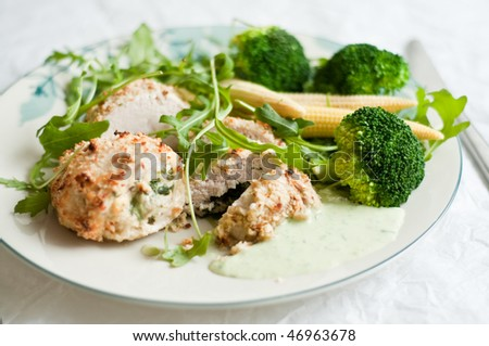 Rolls of chicken breasts and vegetables on the plate - stock photo
