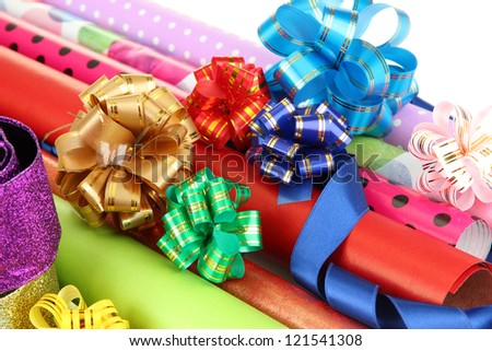 Rolls of Christmas wrapping paper with ribbons, bows isolated on white - stock photo