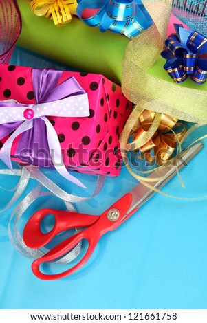 Rolls of Christmas wrapping paper with ribbons, bows on color background