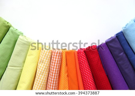 Rolls of colored fabrics lined for the colors of the rainbow.  Rolls of colored fabrics lined for the colors of the rainbow. On a white background.
