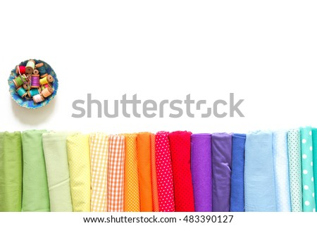 Rolls of colored fabrics lined for the colors of the rainbow. Spools of colored thread lie on a plate.