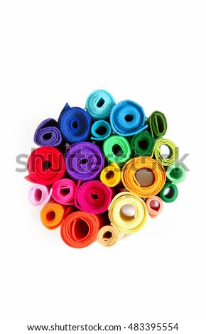 Rolls of colored felt standing on a white background. All the colors of the rainbow.