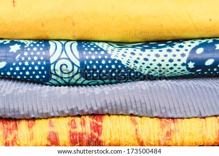 Rolls of colorful asian fabrics as a background image - stock photo