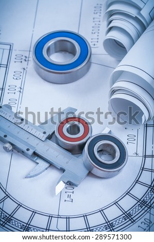 Rolls of construction drawings round rolling bearings and trammel caliper on blueprint industrial concept. - stock photo