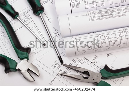 Rolls of diagrams, metal pliers and screwdriver on electrical construction drawing of house, accessories for projects engineer jobs, concept of building house - stock photo