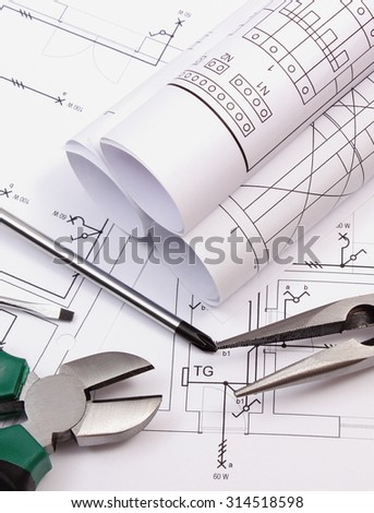 Rolls of diagrams, metal pliers and screwdriver on electrical construction drawing of house, work tool and drawing for projects engineer jobs, concept of building house