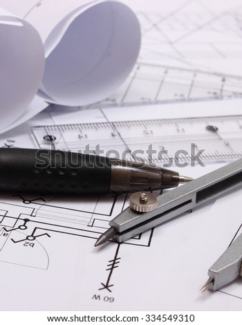 Rolls of electrical diagrams and accessories for drawing lying on construction drawing of house, drawings and accessories for the projects engineer jobs