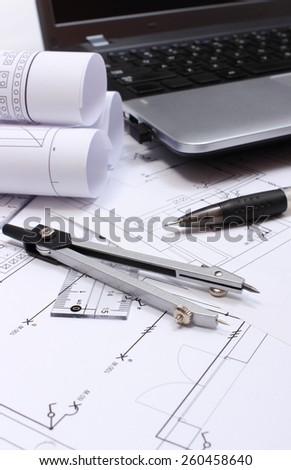 Rolls of electrical diagrams, construction drawings of house, accessories for drawing and laptop, drawings and accessories for the projects engineer jobs - stock photo