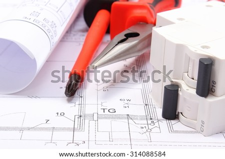 Rolls of electrical diagrams, electric fuse and work tools lying on construction drawing of house, drawings for the projects engineer jobs - stock photo