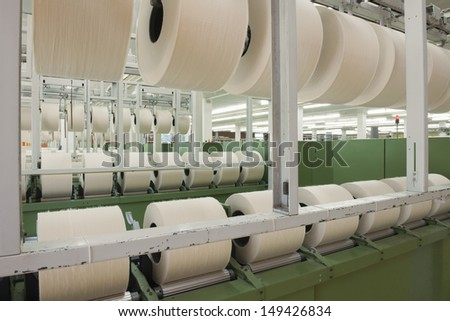 Rolls of fabric and machinery in spinning factory - stock photo
