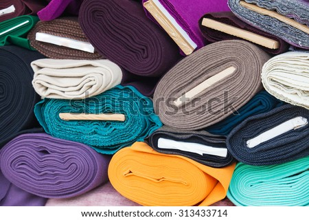 Rolls of fabric and textiles in a factory shop. Multi different colors and on the market. - stock photo