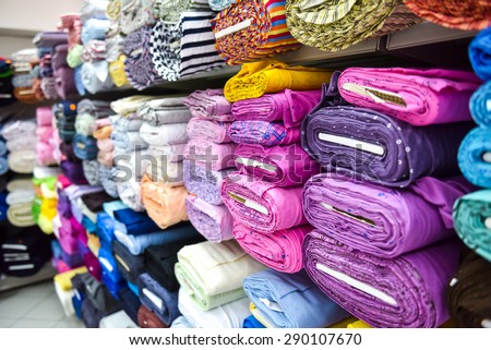 Rolls of fabric and textiles in a factory shop. Multi different colors and patterns on the market. - stock photo