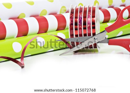 Rolls of gift wrapping paper and rolls of ribbon - stock photo