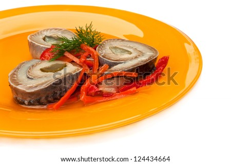 Rolls of herring fillets with pickled cucumber and pepper on a yellow plate