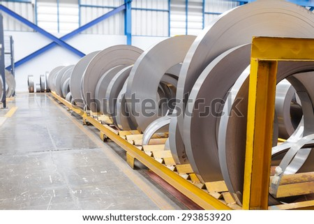 Rolls of metal sheet waiting for assembly in factory - stock photo