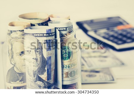 Rolls of money, US dollar bills, in the glass jar with blur calculator background - financial, business, investment and accounting concepts - stock photo