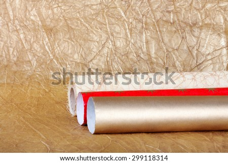 Rolls of multicolored wrapping paper for gifts on gold abstract background.