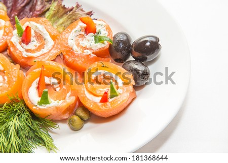 rolls of red fish on a white plate - stock photo