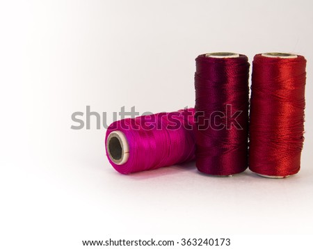 Rolls of red thread with needles. Close up.