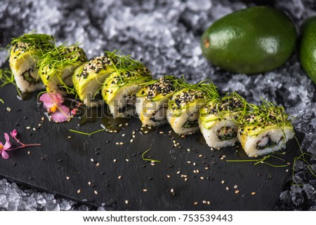 Rolls of seafood in a black plate on ice. Orient asian cuisine. Delicious dinner in a plate close-up on a light background. Healthy fresh food.