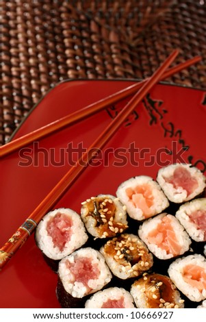 Rolls of sushi on decorative platter with chopsticks