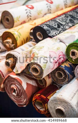 Rolls of tissues at traditional textile covered market with multiple different colors and textures - stock photo