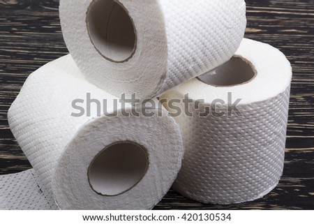 Rolls of toilet paper on wooden board - stock photo