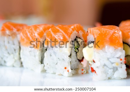 Rolls, sushi and ginger on a white plate and a light background.