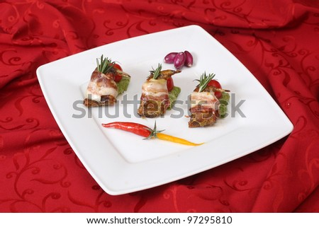 Rolls with bacon and fresh vegetables on a white plate - stock photo