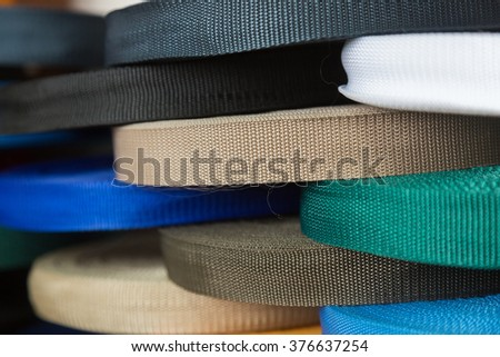 Rolls with color synthetic thread straps. Sewing production furniture - stock photo