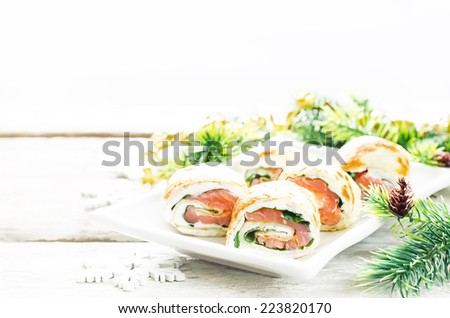 rolls with salmon, spinach and cream cheese on a light woody background. tinting. selective focus on the front roll - stock photo