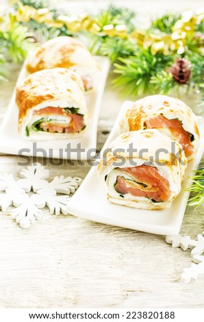 rolls with salmon, spinach and cream cheese on a light woody background. tinting. selective focus on the right roll - stock photo