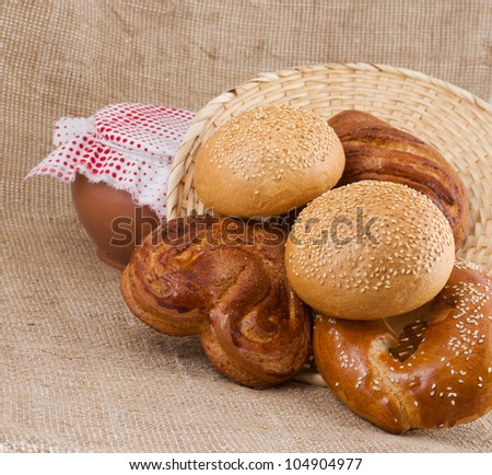 rolls with sesame and cinnamon of pour from a basket on a background sacking and  pot from clay