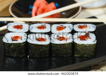 Rolls with the eel meat and hot sauce on a wooden stand